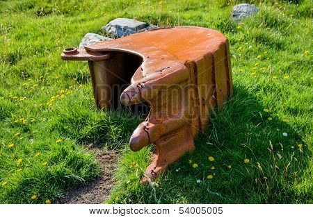 Left behind excavator shovel overgrown with grass