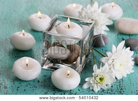 Decorative vase with candles, water and stones on wooden table close-up