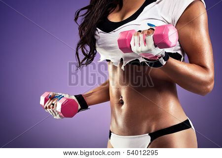 Woman with flat and sexy stomach working out with a dumbbell