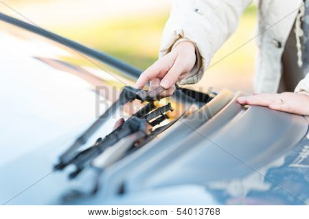 Woman's hand picking up windscreen wiper