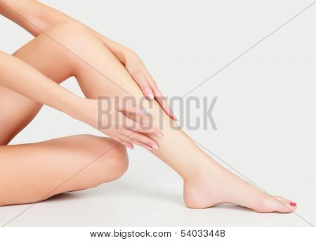 Woman sits on the floor and touches leg by hands