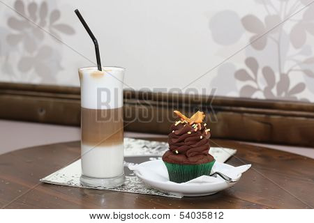 Tasty cupcake with shake on table