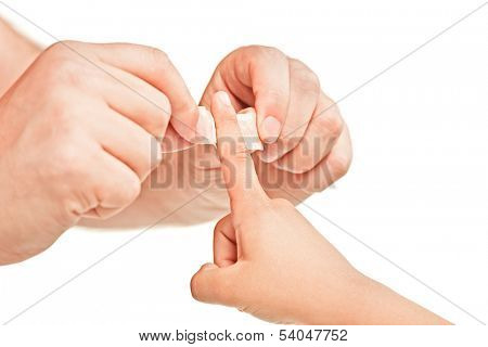 Dad putting a plaster on his sons finger isolated on white background