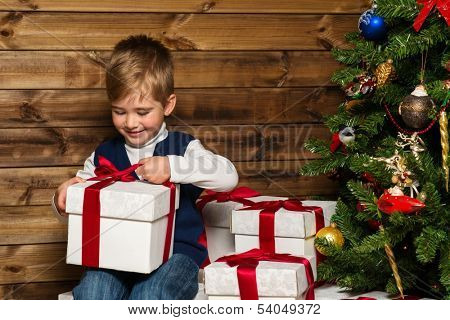 Little boy opening gift box under christmas tree in wooden house interior