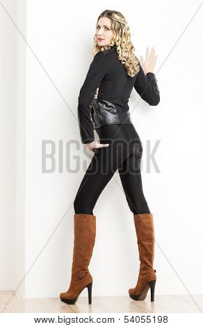 standing woman wearing fashionable clothes and boots