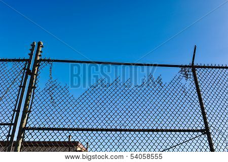 Old Broken Cyclone Fence Against Blue Sky