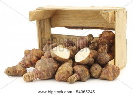 bunch of topinambur roots (helianthus tuberosus) and a cut one in a wooden crate on a white background