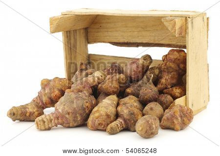 bunch of topinambur roots (helianthus tuberosus) in a wooden crate on a white background
