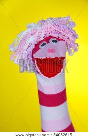 Cute sock puppet on yellow background