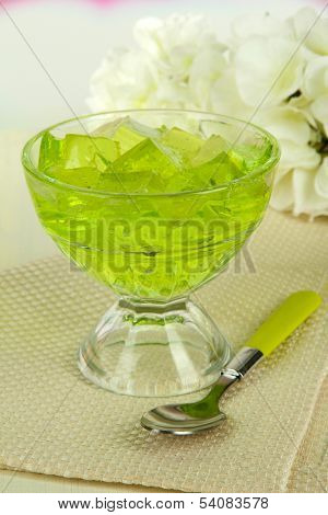 Tasty jelly cubes in bowl on table on light background