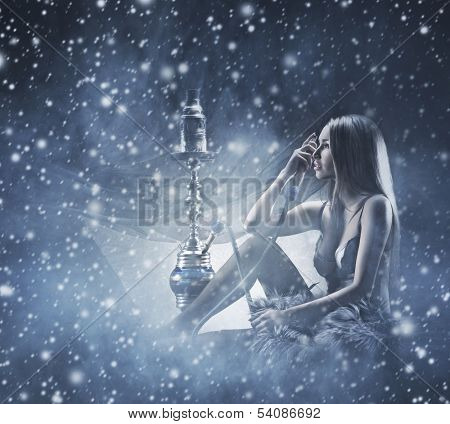 Young and beautiful woman in sexy lingerie smoking the hookah over the winter background