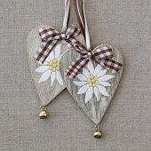 Two hearts with edelweiss on grey fabric background