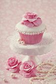 stock photo of ice-cake  - Cupcake with rose flower on a stand - JPG