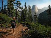 Hiker Walking on Trail with Half Dome in the Background