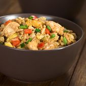 stock photo of rice  - Homemade Chinese fried rice with vegetables chicken and fried eggs served in a brown bowl  - JPG