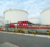 stock photo of petrol  - large storage tanks for oil and petrol in the amsterdam harbor area. The red pipelines are for water supply in case of an fire emergency