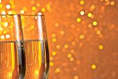 stock photo of flute  - pair of a champagne flutes on orange and yellow light bokeh background with space for text - JPG