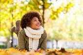 stock photo of down jacket  - Autumn outdoor portrait of beautiful African American young woman lying down  - JPG