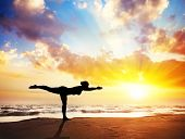 foto of yoga  - Yoga virabhadrasana III warrior pose by woman in silhouette with sunset sky background - JPG