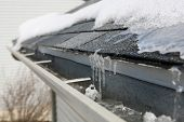 stock photo of frozen  - Ice on roof and gutters - JPG
