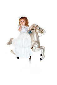 stock photo of carousel horse  - Little girl sits on a carousel horse wearing a long white dress - JPG