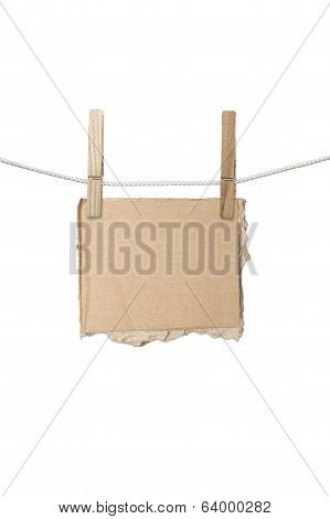 Ripped Piece Of Card Board Hanging On Two Clothespins, Isolated On White