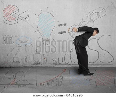 Man Carrying Money Symbol With Business Doodles On Wall