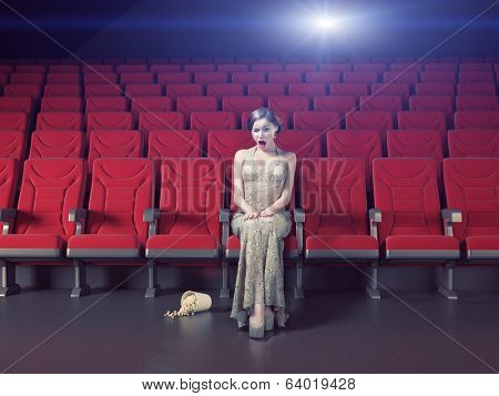 Surprised beautiful girl in an empty cinema. Creative concept