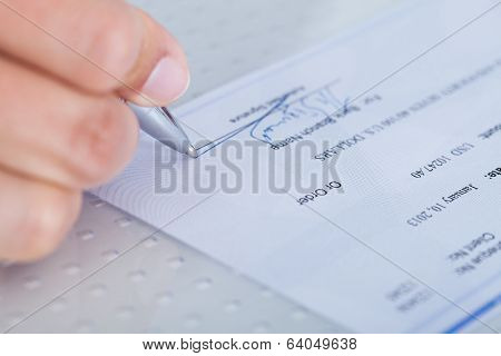 Close-up Of Hand Filling Cheque