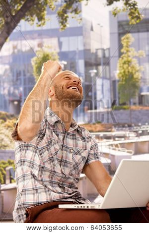 Young man shouting happy while sitting outdoors, using laptop computer, clenched fist.
