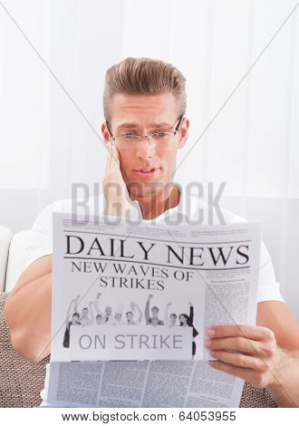 Reading Newspaper With The Headline Strike