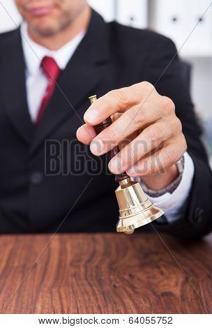 Businessman Holding Bell