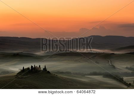 Early dawn in the Tuscan hills near Pienza with villa still in darkness