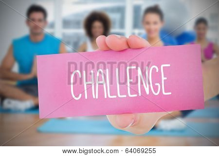 Woman holding pink card saying challenge against yoga class in gym