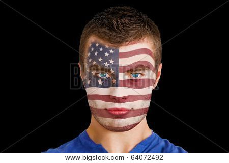 Composite image of serious young usa fan with facepaint against black