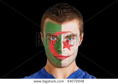 Composite image of serious young algeria fan with facepaint against black