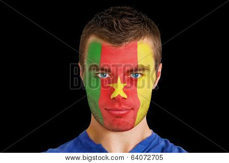 Composite image of serious young cameroon fan with facepaint against black