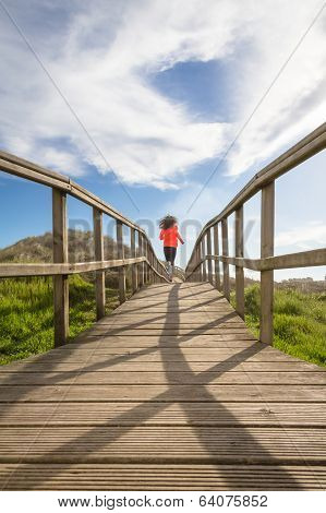 Back view of girl running in a wood boardwalk