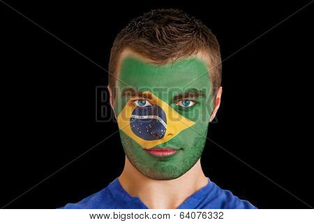 Composite image of serious young brasil fan with facepaint against black