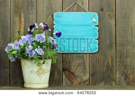 Blank antique blue sign by pot of purple flowers (pansies)