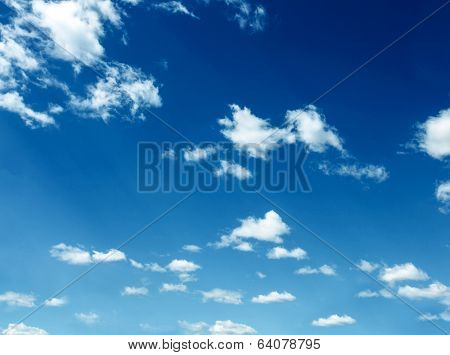 Abstract background of beautiful curly and sparse clouds like whitecaps over light bright blue sky in sunny spring clear day