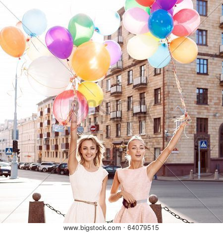 Two Beautiful Ladys In Retro Outfit Holding A Bunch Of Balloons On The Street