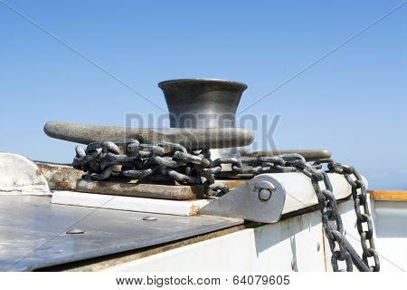 A boats anchor chain is wrapped and secured around a steel cleat as the boat motors across the ocean.