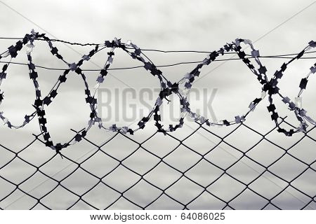 Barbed wire against a stormy sky.