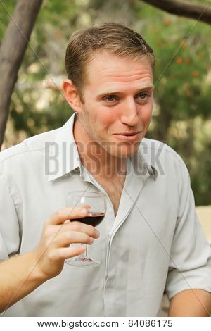 young happy white caucasion man taste and enjoy red wine outdoor in in countryside . classic style fashion.