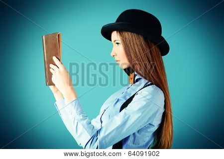 Elegant girl model in blouse, bow tie and bowler hat reading a book. Refined style of old Europe.