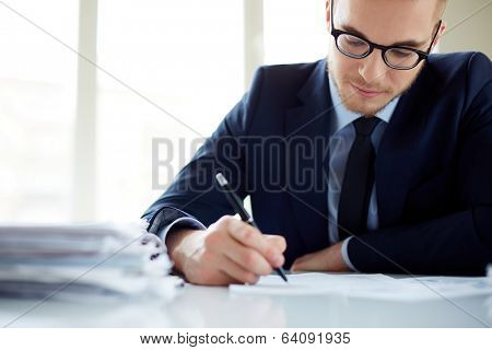 Portrait of handsome office worker making notes