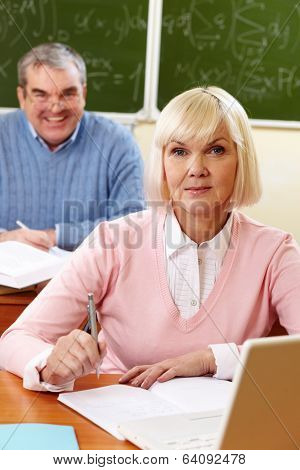 Portrait of blond female looking at camera with senior man on background
