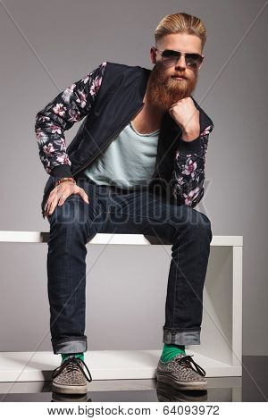 casual young man with a long red beard sitting like the thinker and looking into the camera. in a gray background studio