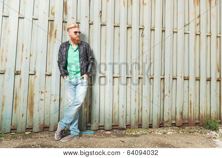 full length portrait of a young casual redhead bearded man standing outdoor with his hands in his pockets and looking away from the camera
